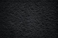 Mörk svart kritiserar med den gråa stenen för bakgrund, delikat naturmodelltextur arkivbilder