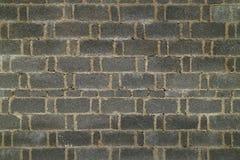 Mörk tegelstenvägg i porslin Arkivfoto