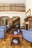 Mörk trätabell mellan blåa fåtöljer i lyxig vardagsruminre med soffan Verkligt foto fotografering för bildbyråer