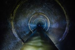 Mörk underjordisk tunnel för avklopprundabetong För kastavklopp för industriellt avloppsvatten och för stads- kloak flödande rör royaltyfria bilder