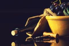 Mörk vinexponeringsglas, druvor och öppnare Fotografering för Bildbyråer