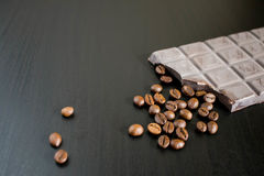 Mörka choklad- och kaffebönor på den gamla trätabellen Royaltyfria Bilder