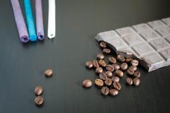 Mörka choklad- och kaffebönor på den gamla trätabellen Royaltyfria Foton