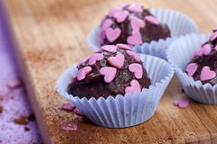 Mörka chokladpralines med rosa hjärtor arkivfoto