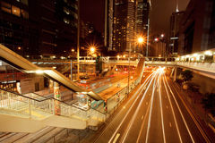 Mörka gator med hotell, skyskrapor och rörelselinjer nära stadsspårvagnen stoppar Royaltyfri Fotografi