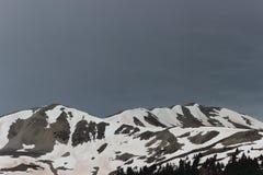 Mörka himlar ovanför de steniga bergen royaltyfri foto