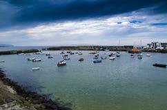 Mörka himlar på den Portrush hamnen Arkivbild