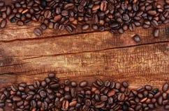 Mörka kaffebönor på trä Royaltyfria Bilder