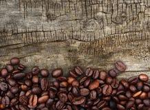 Mörka kaffebönor på trä Royaltyfri Foto