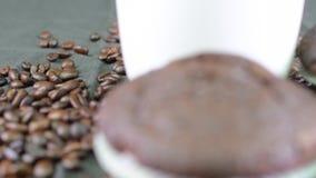 Mörka muffin-, kopp kaffe- och kaffebönor på svart bakgrund lager videofilmer