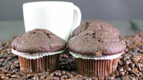 Mörka muffin-, kopp kaffe- och kaffebönor på svart bakgrund arkivfilmer