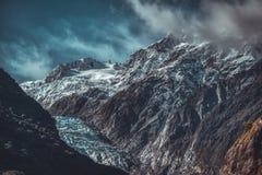 Mörka ojämna berg och Franz Josef Glacier royaltyfria bilder
