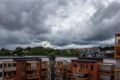 Mörka sommarstormmoln över bostads- stadsbyggnader och tak royaltyfri foto