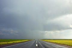 Mörka stormiga himmel och moln och en våt väg i regnet Arkivbilder