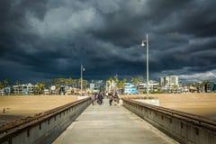 Mörka stormmoln över den fiskepir och stranden i Venedig Beac fotografering för bildbyråer
