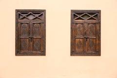 Mörka trästängda fönster som kontrasterar till väggen för ljus kräm royaltyfri foto