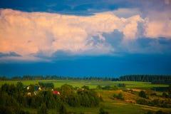 Mörker - blå cloudscape över gräsplanfält för storm arkivbilder