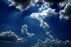 Mörker - blå himmel och vitmoln arkivbilder