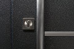 Mörker - blå metallisk dörr med det långa handtaget och nyckelhålet Royaltyfri Bild