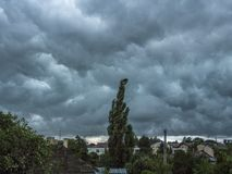 Mörker - blå stormig himmel under hushåll Bakgrund royaltyfria foton