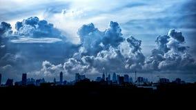 Mörker - blåa stormmoln över stad i regnig säsong Royaltyfria Bilder
