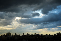 Mörker - blåa stormmoln över stad i regnig säsong Arkivfoton