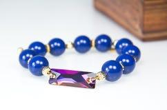 Mörker - blått prytt med pärlor armband med den guld- omfamningen royaltyfri foto