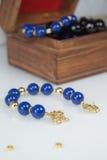 Mörker - blått prytt med pärlor armband med den guld- omfamningen royaltyfria foton