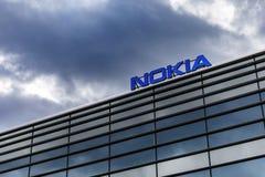 Mörker fördunklar över den Nokia logoen överst av en byggnad royaltyfri fotografi
