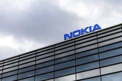Mörker fördunklar över den Nokia logoen överst av en byggnad royaltyfria foton