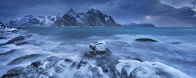 Mörker fördunklar över en fjord i Norge i vinter royaltyfri fotografi
