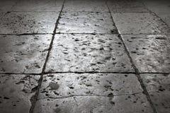 Mörker - grå sten som belägger med tegel på golvet, bakgrund arkivfoton