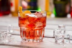 Mörker - orange drink i exponeringsglas arkivfoto