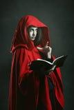 Mörker - röd med huva häxa som läser en bok royaltyfri fotografi