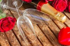 mörker - röda rosor med halsen av champagne Arkivfoto