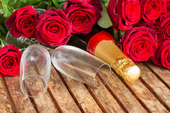 mörker - röda rosor med halsen av champagne Arkivbild
