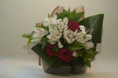 Mörker - röda rosor och blommor på gröna skor på hälet Royaltyfri Foto
