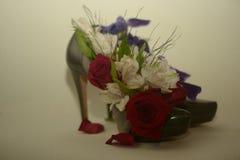 Mörker - röda rosor och blommor på par av gröna skor Royaltyfri Fotografi