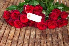 Mörker - röda rosor och etikett Royaltyfria Foton
