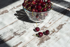 Mörker - röda söta körsbär i genomskinlig bunke Arkivbilder