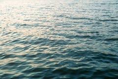 Mörker - yttersida för blått vatten med solnedgångljusredlection Havs- eller havvattenbakgrund royaltyfri fotografi