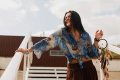 Mörkhyad flicka med en dröm- stoppare på kusten royaltyfri bild