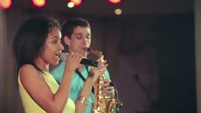 Mörkhyad svart kvinnasångare och tunn saxofonspelare som utför på etapp stock video