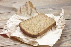 mörkt bröd med smulor på det wood brädet kraft papper Skorpabröd royaltyfria foton