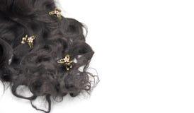 Mörkt brunt lockigt hår med koppar och kristallsmycken på den vita bakgrunden arkivfoto