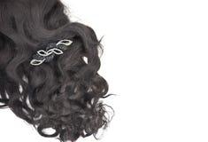 Mörkt brunt lockigt hår med kristallhårspännen på den vita bakgrunden royaltyfri bild