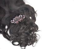 Mörkt brunt lockigt hår med kristallhårspännen på den vita bakgrunden royaltyfria bilder