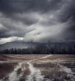 Mörkt dystert landskap med landsvägen i snö Royaltyfria Bilder