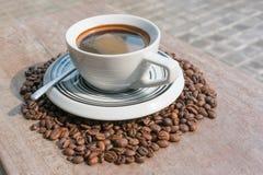 Mörkt kaffe i mitt av kaffebönor Arkivfoton