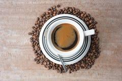 Mörkt kaffe i mitt av kaffebönor Arkivfoto